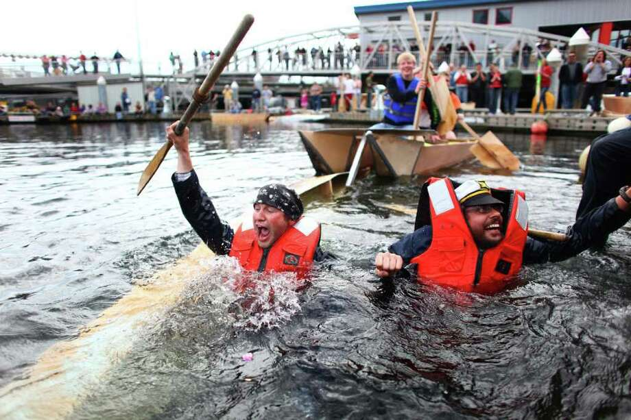From front, Tim Terrill, Sean Baldeschwiler and Cory Thompson end up in the water as the Seattle Maritime Academy's entry tips in the Quick and Dirty Boat Building Competition during the Seattle Maritime Festival on Saturday, May 14, 2011 on the Seattle waterfront. Contestants had to build a boat for under $100 and paddle the boats against other contestants. The annual event featured the boat competition and the popular tugboat races. The event is organized by the Seattle Propeller club and the Port of Seattle and showcases Seattle's maritime industry. Photo: JOSHUA TRUJILLO / SEATTLEPI.COM