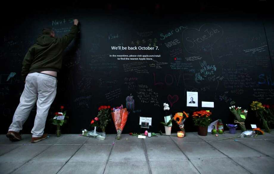 Lee Osborne of Seattle writes a message with chalk on the window of the University Village Apple Store on Thursday, October 6, 2011, the day after Apple co-founder Steve Jobs died. Dozens of messages were written on black plastic covering the windows of the store. The store was being remodeled at the time. Photo: JOSHUA TRUJILLO / SEATTLEPI.COM