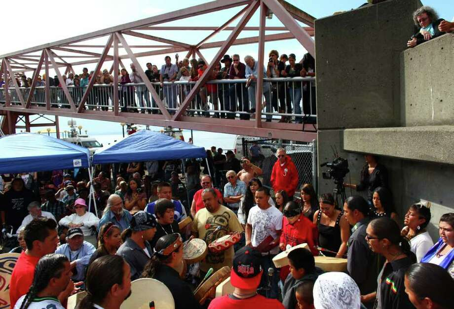 The Sacred Water drum circle performs to honor Native wood carver John T. Williams on Tuesday, August 30, 2011 at Waterfront Park on Pier 57 in downtown Seattle. Williams, a Native woodcarver known to Seattleites for his sought after carvings and known to police for his drinking problem, was shot and killed by a police officer in 2010 when he didn't put down his carving knife when ordered. The officer involved in the shooting resigned when a review board ruled the killing unjustified. The city settled with the family for an undisclosed sum and also allowed the family to carve and erect two Totem poles in Williams' honor. During the gathering the Totem poles were blessed by family members. Photo: JOSHUA TRUJILLO / SEATTLEPI.COM