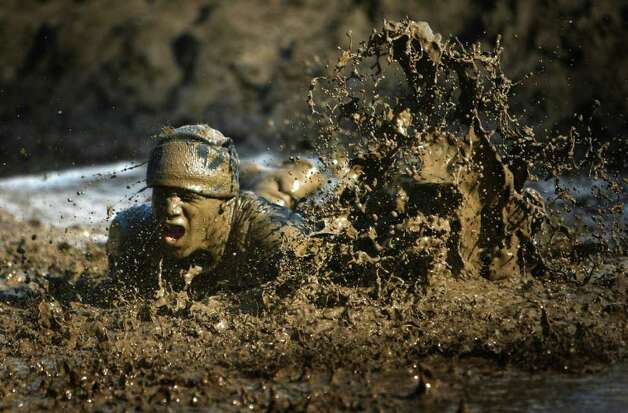 A participant leaps into a mud pit during the Gladiator Rock'N Run on Saturday, October 29, 2011 at Pacific Raceways in Kent. Participants in the five kilometer race ran through obstacles that included an ice bath, mud pit and they had to leap over a fire pit. Photo: JOSHUA TRUJILLO / SEATTLEPI.COM