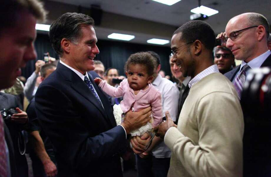 Presidential candidate Mitt Romney lifts Alexandria McDonald, 6 months, daughter of Microsoft employee Orville McDonald, far right, after a speech on Thursday, October 13, 2011 on the Microsoft campus in Redmond. The Republican presidential candidate came to Microsoft as part of a speaker series and talked about trade policy. Photo: JOSHUA TRUJILLO / SEATTLEPI.COM