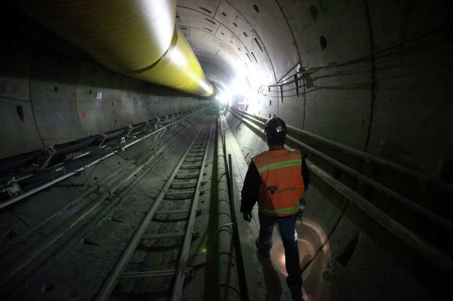 A project manager walks under the Montlake Cut during a tour of Sound Transit's tunneling operation from the University of Washington to Capitol Hill on Wednesday, October 11, 2011 in Seattle. The tunnel boring machine had traveled about 2,000 feet since it began operation at the University of Washington station next to Husky Stadium.  The two 21 foot diameter tunnels from the UW to Capitol Hill will eventually be two miles long. It is planned to be completed in 2016. Photo: JOSHUA TRUJILLO / SEATTLEPI.COM