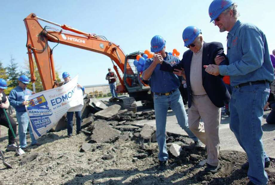 Dick Spady, founder of Dick's Drive-In, is helped across broken pavement during the groundbreaking for the new Dick's Drive-In on Thursday, May 19, 2011 on Highway 99 in Edmonds. The restaurant was the first new Dick's to open since 1974. Photo: JOSHUA TRUJILLO / SEATTLEPI.COM