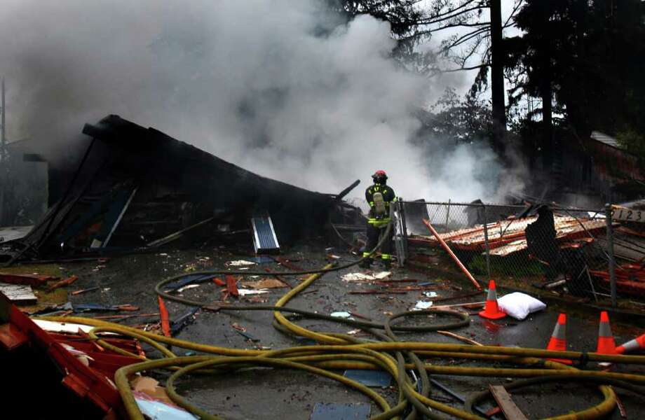 Firefighters work the scene after a house exploded on Monday, September 26, 2011 in Seattle's Pinehurst Neighborhood. A natural gas leak caused the explosion that turned the house into rubble, injuring two occupants. Leaks were later discovered throughout the neighborhood and were suspected to be caused by electricity from a downed power line contacting the gas lines. Photo: JOSHUA TRUJILLO / SEATTLEPI.COM