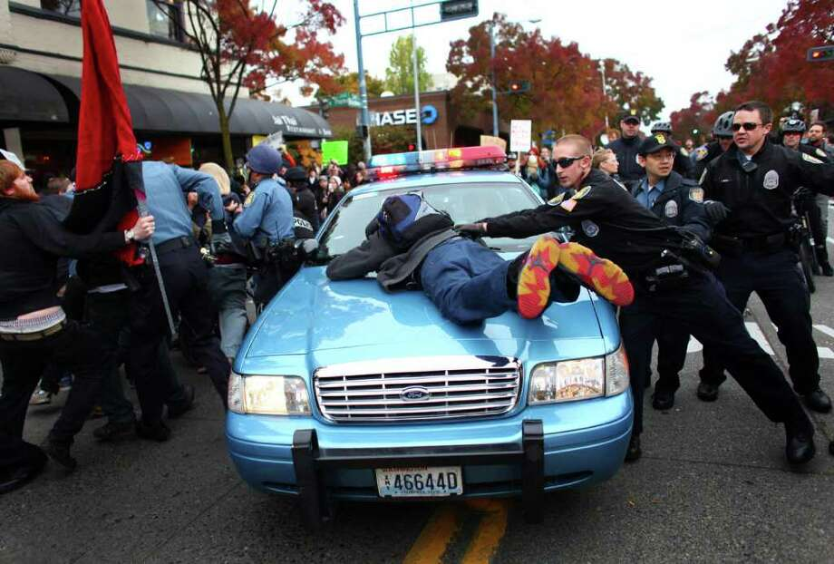 A man jumps onto the hood of a police cruiser as police try to remove an arrested protester during an Occupy protest outside a Chase Bank branch on Broadway Avenue East and East Thomas Street on Wednesday, November 2, 2011. Protesters connected themselves together with pipes inside the branch. When they were removed from the bank a mini-riot ensued as police worked to keep back protesters. Chase CEO Jamie Dimon was visiting Seattle for a later event at the Sheraton Hotel. Photo: JOSHUA TRUJILLO / SEATTLEPI.COM
