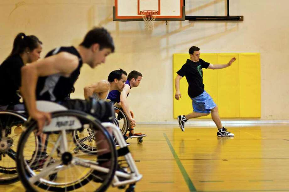 Players follow coach Christian Burkett while doing speed drills at the Miller Community Center in Seattle on July 12, 2011 during wheelchair basketball. Photo: JOE DYER / SEATTLEPI.COM