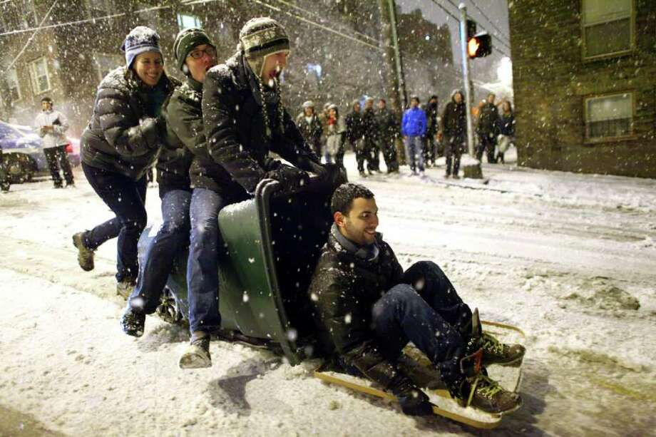People begin the trip down East Denny Way in a recycling bin in Seattle's Capitol Hill neighborhood on Tuesday, January 11, 2011 as snow blankets Seattle. The treacherous hill is a favorite spot for sledders and also a place where cars regularly careen out of control during snow storms. Photo: JOSHUA TRUJILLO / SEATTLEPI.COM