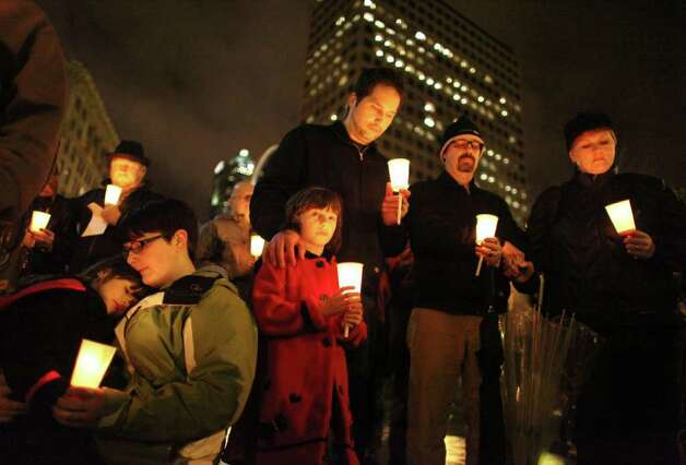 From left, Ava Picasso, 4, Amber Miller, Livia Picasso, 6, Brent Picasso, Scott Miller and Karina Miller hold candles during a memorial at Seattle's Westlake Park on Thursday, January 13, 2011. Ava and Livia are great-granddaughters of 76-year-old Dorwan Stoddard, a former Sequim resident who was killed during a shooting rampage in Tucson that targeted a U.S. congresswoman. The shooting stunned the nation and prompted an outpouring of support for the victims and their families across the nation. Photo: JOSHUA TRUJILLO / SEATTLEPI.COM