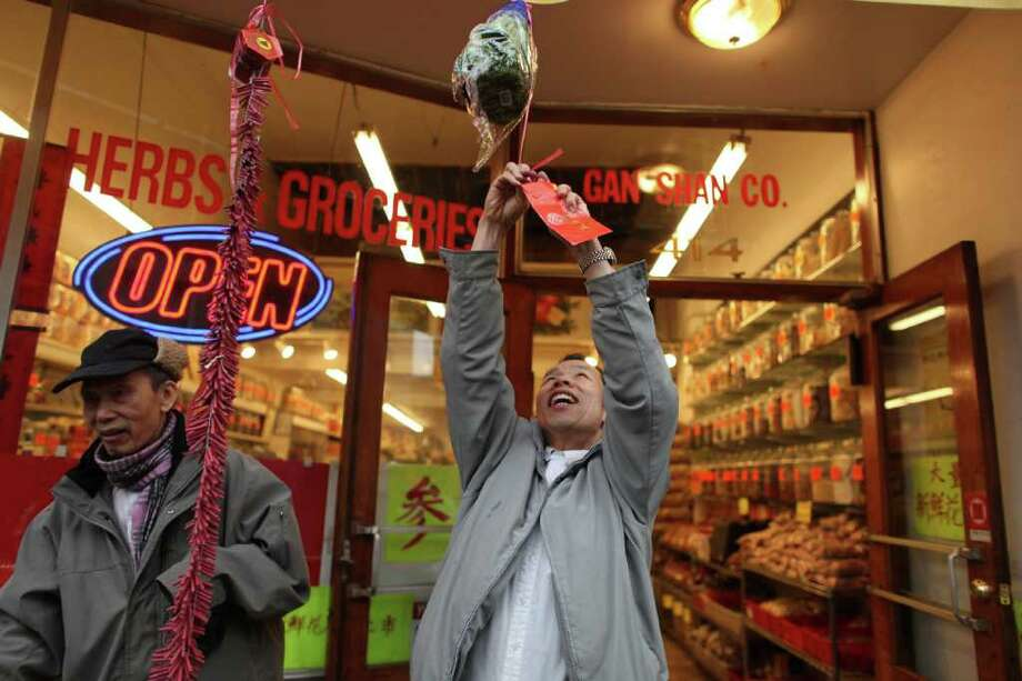 A business owner affixes a gift to the front of his business as members of the Mak Fai Washington Kung Fu Club perform a lion dance during the Year of the Rabbit Lunar New Year celebration in Seattle's International District on Saturday, Jan. 29, 2011. Photo: JOSHUA TRUJILLO / SEATTLEPI.COM