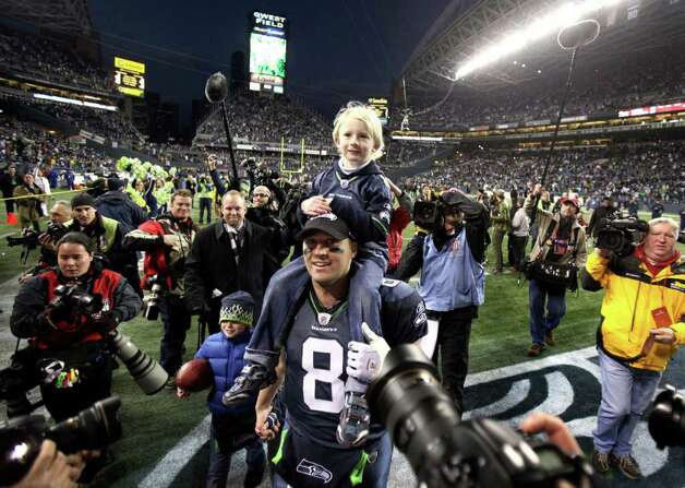 Seattle Seahawks quarterback Matt Hasselbeck walks off the field with his son Henry on his shoulders after defeating the defending Super Bowl Champion New Orleans Saints. This was Hasselbeck's last appearance at Qwest Field as he later left to play for the Tennessee Titans. Photo: JOSHUA TRUJILLO / SEATTLEPI.COM
