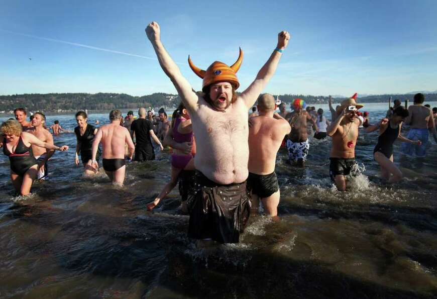 A participant raises his arms during the annual Polar Bear Plunge at Matthews Beach on Lake Washingt