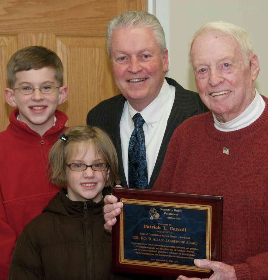Southport Harbor Master Patrick L. Carroll Jr., right, holds recent leadership award from the Connecticut Harbor Management Association, as he is congratulated by First Selectman Michael Tetreau and his great-grandchildren Aidan and Molly McLaughlin. Photo: Hugh Smith / Fairfield Citizen contributed