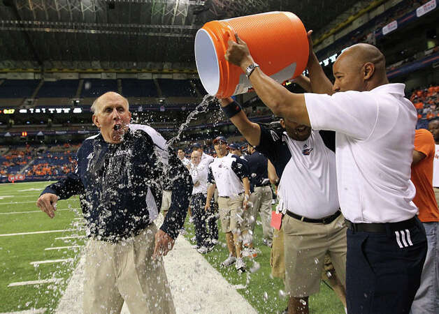 UTSA head coach Larry Coker (left) gets doused with water by assistant coach Nathaniel Jones (right) and equipment manager Scott Bajek in the closing moments of their game against Minot at the Alamodome on Saturday, Nov. 19, 2011. UTSA defeated Minot 49-7 for a victory to end their inaugural season. Photo: Kin Man Hui / San Antonio Express-News