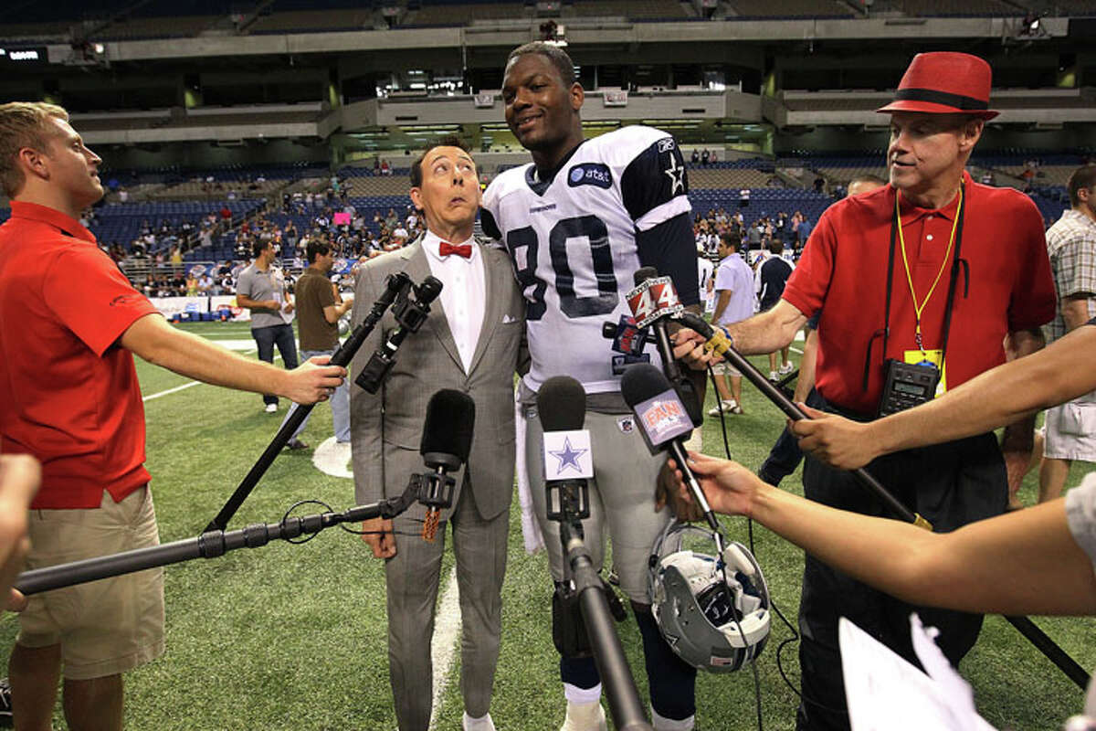 Comedian Pee Wee Herman (left) makes a face while posing for a picture with Cowboys tight end Martellus Bennett (80) at the evening session of the Dallas Cowboys training camp at the Alamodome on Thursday, Aug. 4, 2011.