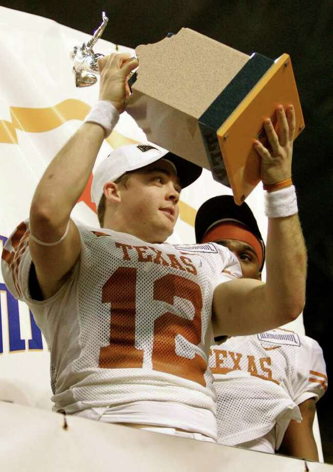 Texas quarterback Colt McCoy displays the offensive-player-of-the-game trophy after his team defeated Iowa during the Alamo Bowl on Saturday, Dec. 30, 2006. WILLIAM LUTHER / STAFF