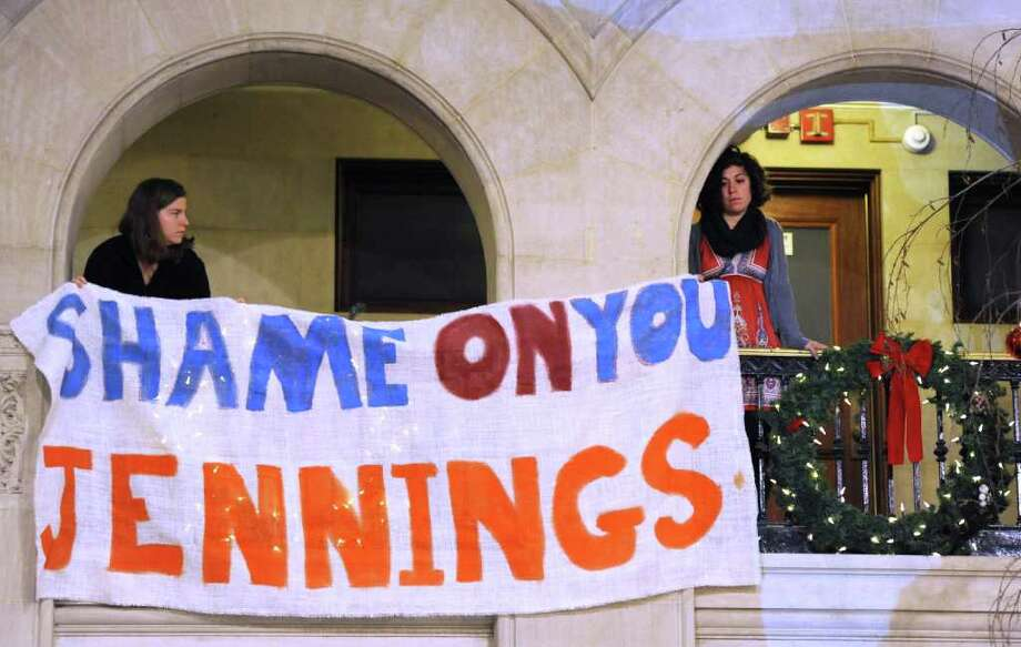 Members of the Occupy Albany hang a sign out from the second level of City Hall during a press conference in Albany, N.Y. Dec. 28, 2011.   ( Skip Dickstein/Times Union) Photo: Skip Dickstein / 2011