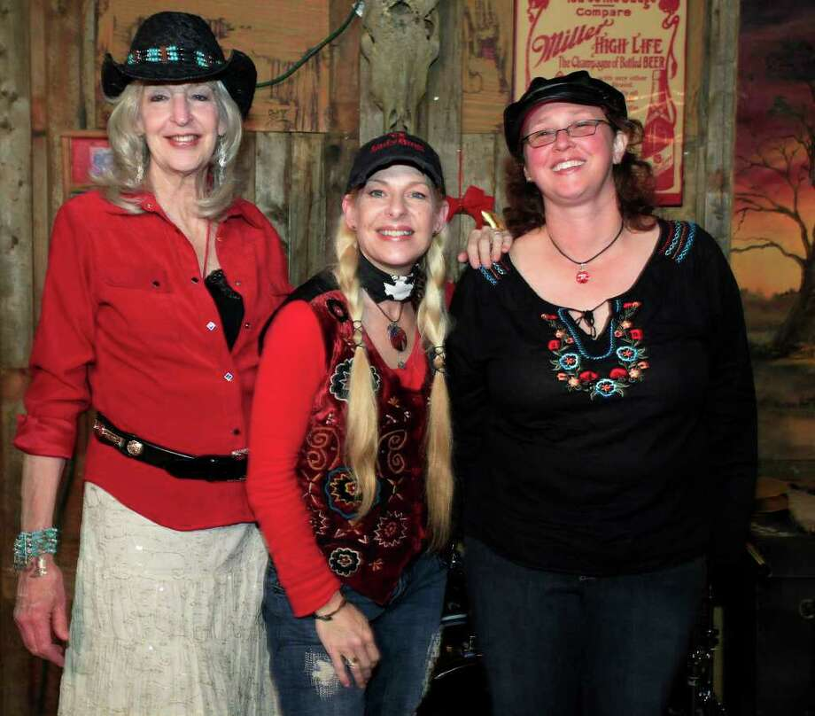 Susan Taylor (from left), Katherine Dawn and Ginger Pickett get together during the Texas Music Coalition Holiday Party Showcase at The Hangin' Tree Saloon. Photo: For The Express-News, J.Michael Short