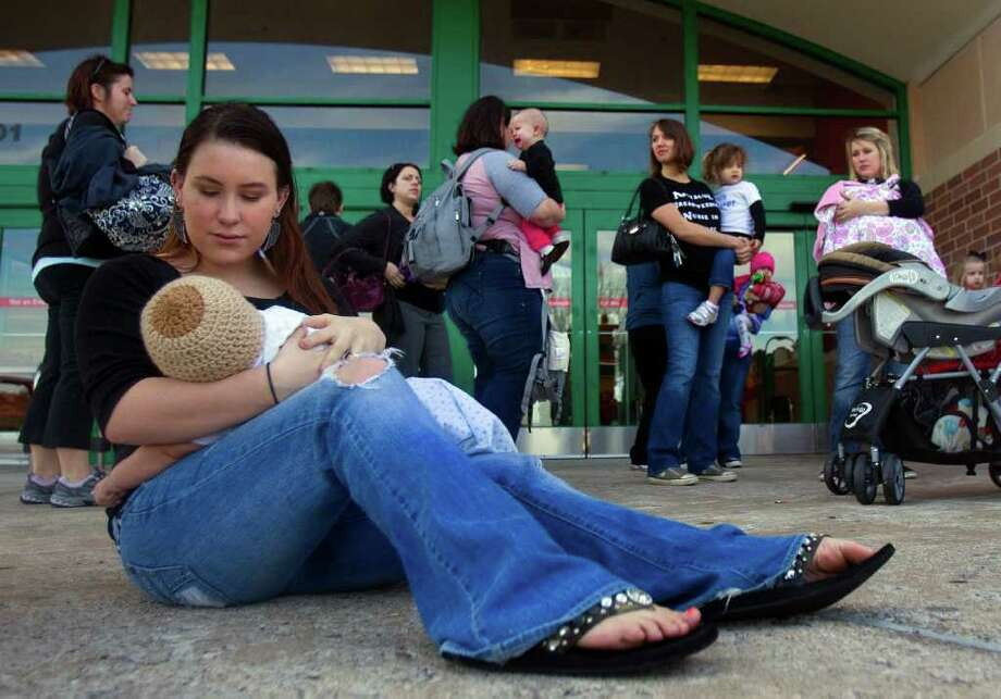 "Brittany Hinson breast feeds her 4-month-old son, Kennedy, during a ""nurse-in"" in front of the Webster Super Target store Wednesday, Dec. 28, 2011.  Hinson participated in the event in support of breast feeding and in support of a Houston woman Michelle Hickman after she was approached by Target employees for breastfeeding in the store. ""It's not like she was walking around topless,"" Hinson said. ""She was sitting down covered up."" Photo: Cody Duty, Houston Chronicle / © 2011 Houston Chronicle"