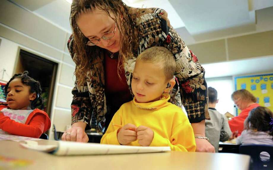 Cindy Lauer encourages young Dillon Goddard at the Sunshine Cottage School for Deaf Children. As a child, Lauer attended the school and was taught by Blane Trautwein, who was then a new teacher embarking on his career. Photo: BILLY CALZADA, SAN ANTONIO EXPRESS-NEWS / gcalzada@express-news.net