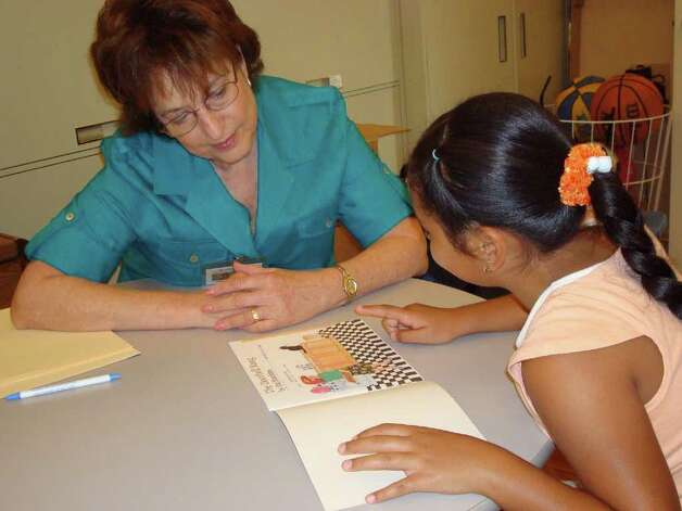 Tutor Alma Green of SA Reads helps a young girl with her reading. Photo: COURTESY PHOTO