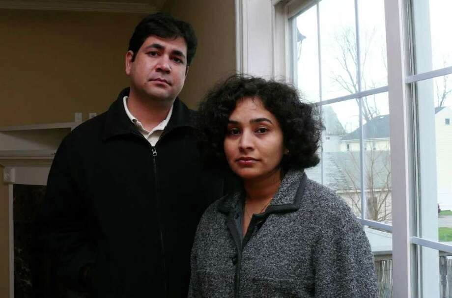 Rajnish and Vandana Jain stand in the living room of their Brentwood Avenue condo, rendered uninhabitable by a fire in May. The couple learned that the condo associatioin manager had let the master insurance policy for the four-unit development expire, leaving them unable to make structural repairs. Photo: Genevieve Reilly / Fairfield Citizen
