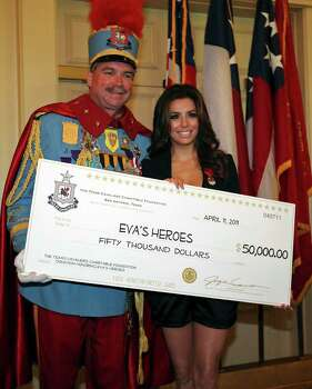 FOR METRO - King Antonio LXXXIX Bill Mitchell (left) and Eva Longoria pose for pictures with a check for fifty thousand dollars that Mitchell presented to Longoria for her charity Eva's Heroes at the Westin Riverwalk Monday April 11, 2011. (PHOTO BY EDWARD A. ORNELAS/eaornelas@express-news.net) Photo: EDWARD A. ORNELAS / SAN ANTONIO EXPRESS-NEWS (NFS)