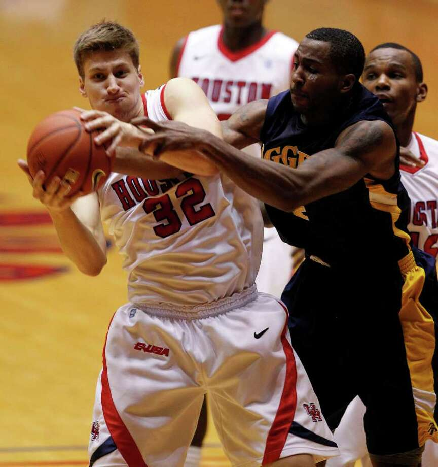 The University of Houston's Kirk Van Slyke left and North Carolina A&T's DaMetrius Upchurch wrestle for a rebound during first half of men's college basketball game action at the University of Houston's Hofheinz Pavilion Wednesday, Dec. 28, 2011, in Houston. Photo: James Nielsen, Chronicle / © 2011 Houston Chronicle