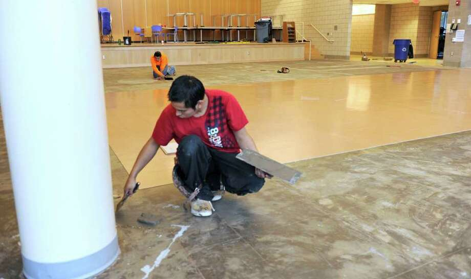 Oscar Arcos lays new floor tile in the new cafe/auditorium of Newtown High School on Wednesday. Contractor Morganti Group Inc. said it expects to complete the school expansion project this week, except for the greenhouse and a few other items that will take up to another six weeks to complete, according to Robert Mitchell, chairman of the Newtown Public Building and Site Commission. Photo taken Wednesday, Dec. 28, 2011. Photo: Carol Kaliff / The News-Times