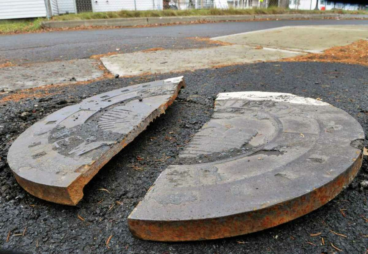 A man hole cover lays broken on Satterlee Lane Wednesday Dec. 28, 2011, from last night's explosions in Fort Edward. (John Carl D'Annibale / Times Union)
