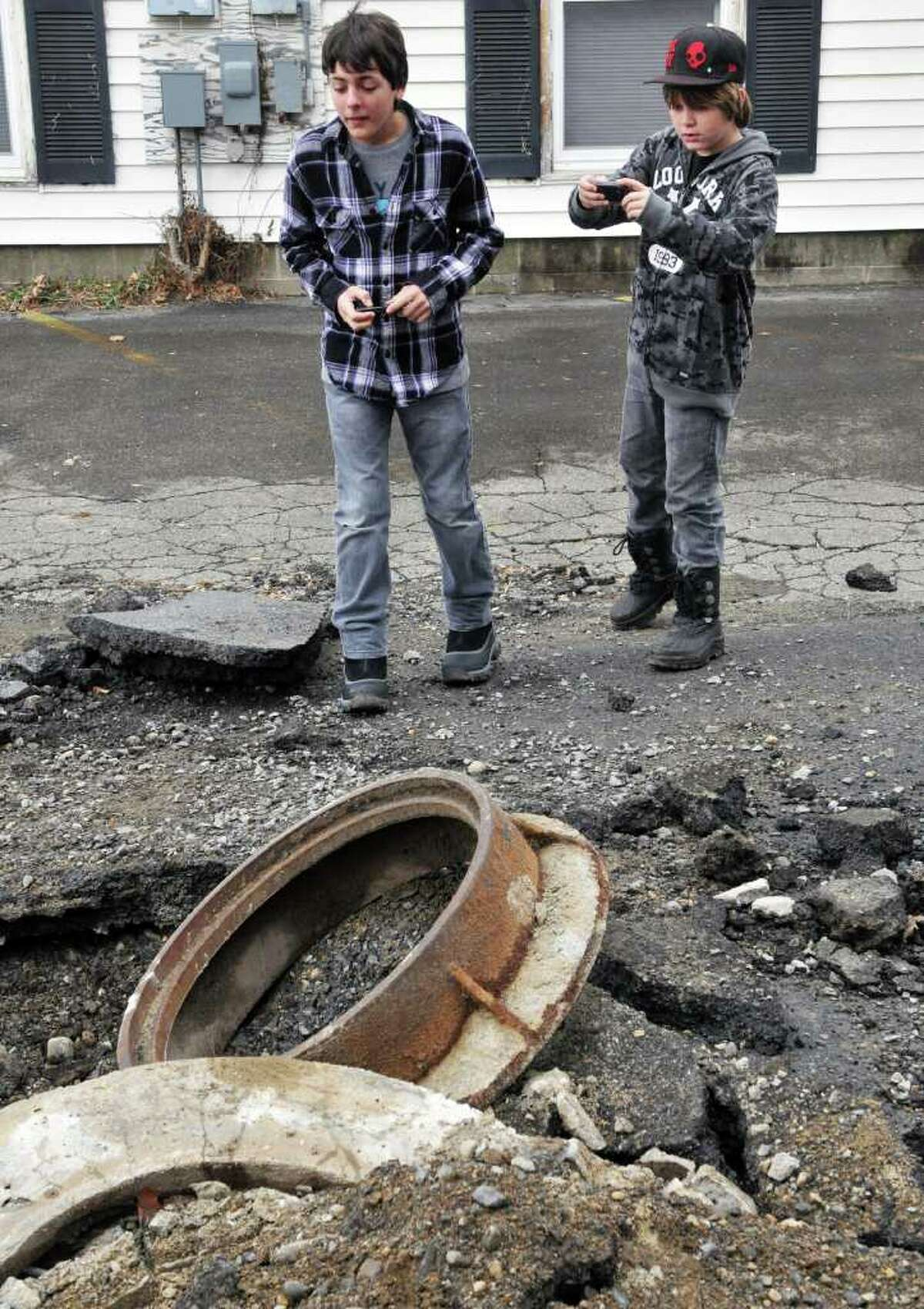 Anthony Cobassani, 12, left, and Luke Gifford, 11, both of Palm Harbor, Fla., use their phones to photograph damage to Satterlee Lane in Fort Edward Wednesday Dec. 28, 2011, from last's night's explosions. The boys were in the area visiting relatives for the holidays. (John Carl D'Annibale / Times Union)