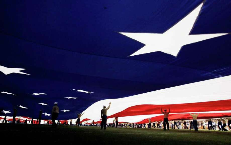 United States Marines hold up a giant flag before the Holiday Bowl NCAA college football game between California and Texas, Wednesday, Dec. 28, 2011, in San Diego. (AP Photo/Gregory Bull) Photo: Gregory Bull, Associated Press / AP