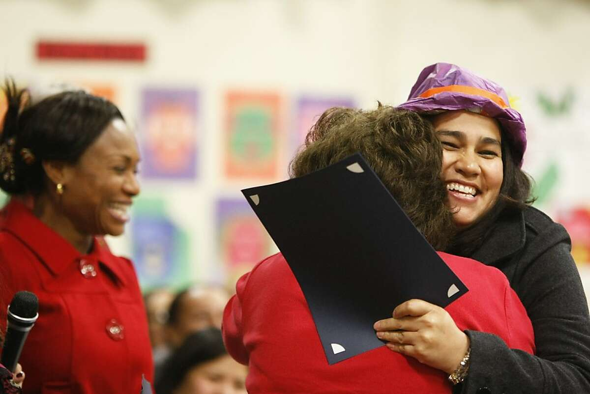 Luisa Ortega hugs SSFUSD PTA President Marta Bookbinder as she receives her diploma from the School Smarts Parent Academy at Sunshine Gardens Elementary School in South San Francisco, Calif., on Thursday, Dec. 15, 2011.