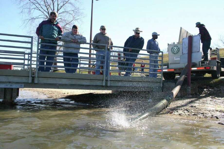 PUMP IT UP: A Texas Parks and Wildlife Department hatchery truck pumps hundreds of rainbow trout into an urban lake near Houston. Photo: Joe Doggett