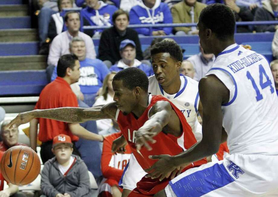 Lamar's Anthony Miles, left, is pressured by Kentucky's Doron Lamb and Michael Kidd-Gilchrist (14) during the first half of an NCAA college basketball game in Lexington, Ky., Wednesday, Dec. 28, 2011. (AP Photo/James Crisp) Photo: (AP Photo/James Crisp), FRE / FR6426 AP