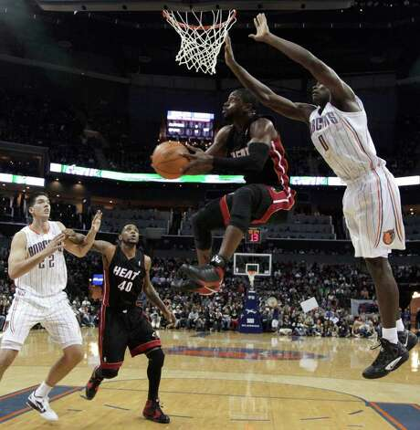 Miami's Dwyane Wade sails to the basket past Charlotte rookie Bismack Biyombo in the second half. Photo: AP