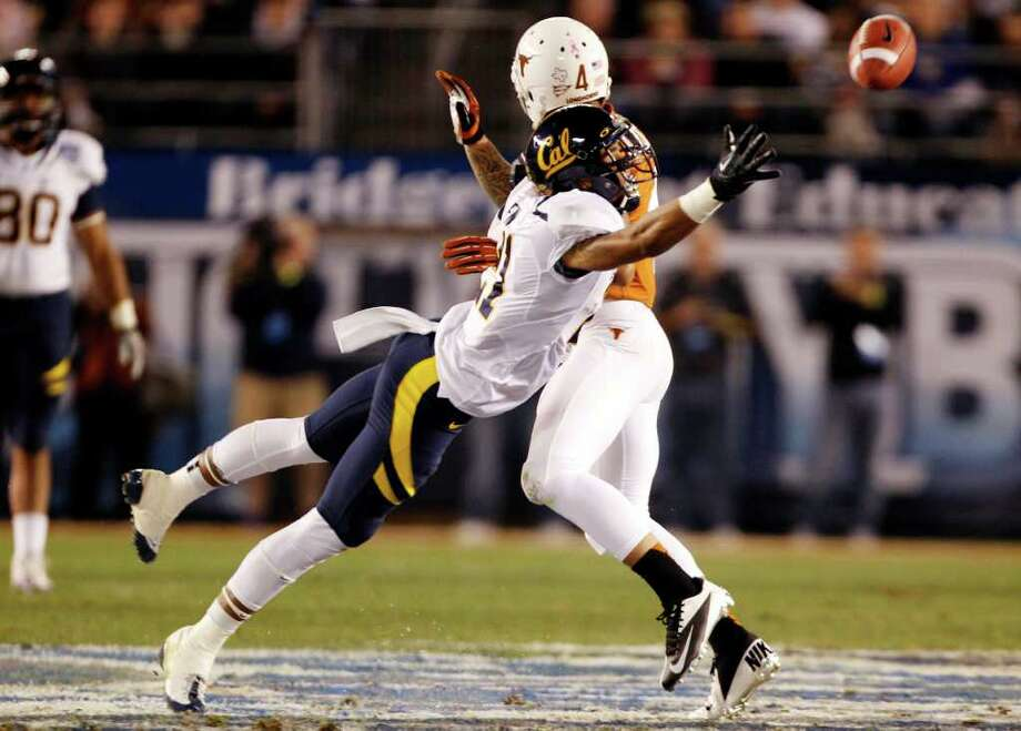 California wide receiver Keenan Allen, front, is blocked on his way to the ball by Texas safety Kenny Vaccaro during the Holiday Bowl NCAA college football game, Wednesday, Dec. 28, 2011, in San Diego. Vaccaro was called for pass interference on the play. (AP Photo/Lenny Ignelzi ) Photo: Lenny Ignelzi, Associated Press / AP
