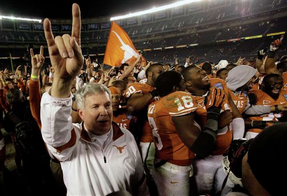 Texas head coach Mack Brown, left, celebrates with his team after beating California 21-10 to win the Holiday Bowl NCAA college football game Wednesday, Dec. 28, 2011, in San Diego. (AP Photo/Gregory Bull)