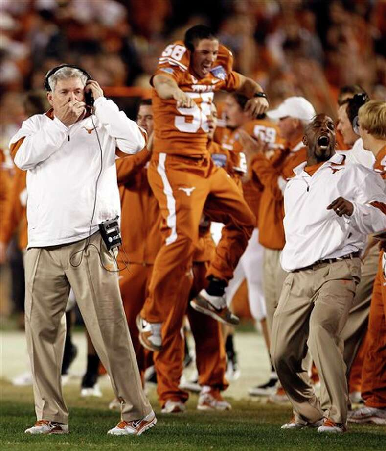 Texas coach Mack Brown, left, communicates on his head set as his assistant coaches and players start to celebrate their 21-10 victory over California in the Holiday Bowl  college football game Wednesday, Dec. 28, 2011 in San Diego. (AP Photo/Lenny Ignelzi ) Photo: Associated Press