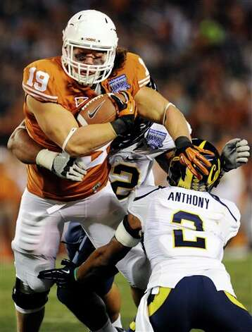 Texas tight end Blaine Irby (19) fends off a tackle from California's Marc Anthony (2) during the second quarter of the Holiday Bowl NCAA college football game, Wednesday, Dec. 28, 2011, in San Diego. (AP Photo/The Dallas Morning News, Elisabeth Dillon)  MANDATORY CREDIT; MAGS OUT; TV OUT; AP MEMBERS ONLY Photo: Associated Press