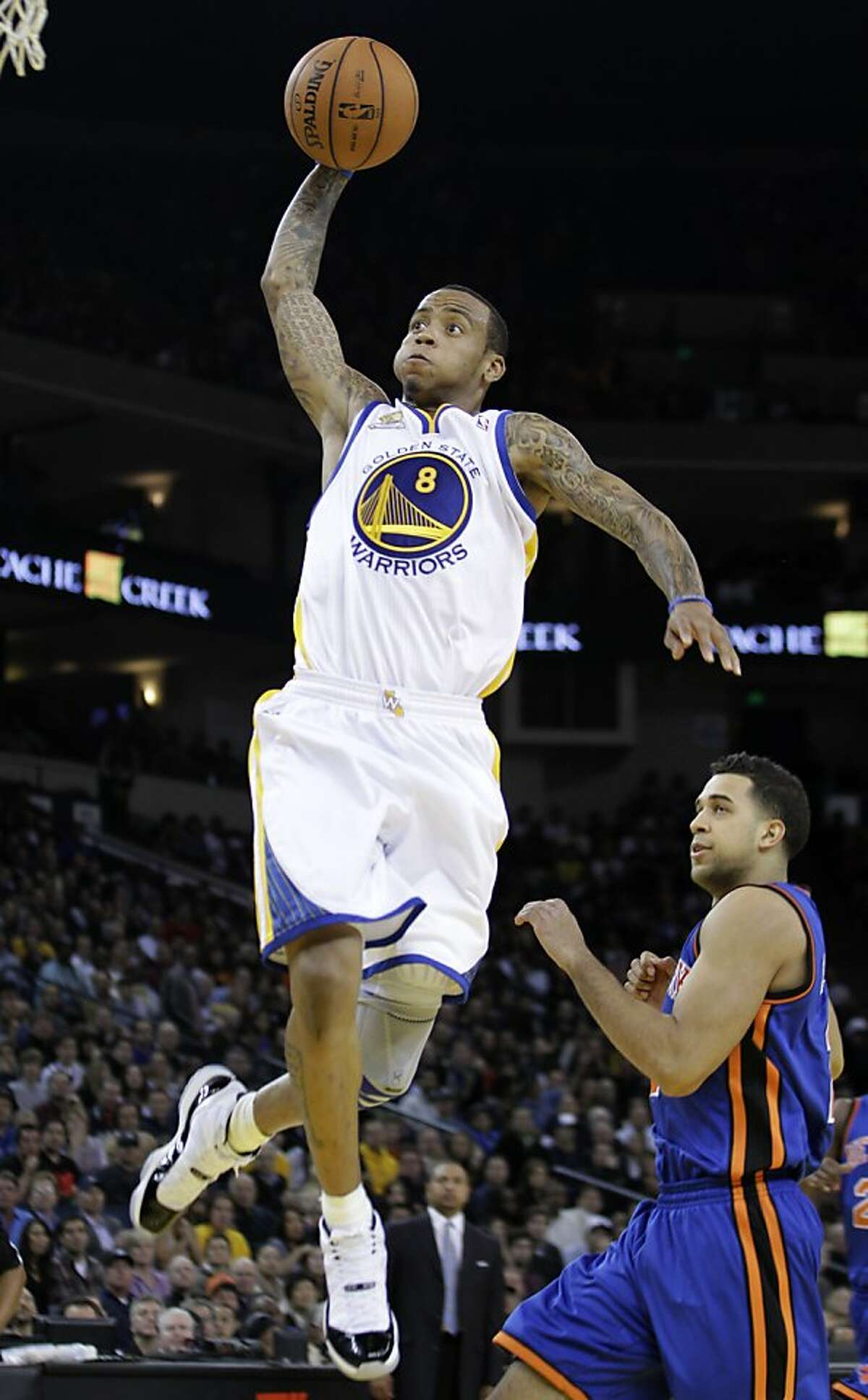 Golden State Warriors' Monta Ellis takes a shot over New York Knicks' Landry Fields during the first half of an NBA basketball game Wednesday, Dec. 28, 2011, in Oakland, Calif. (AP Photo/Ben Margot)
