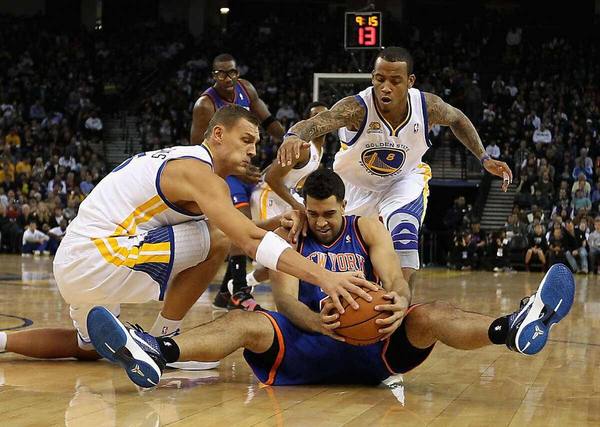 OAKLAND, CA - DECEMBER 28: Landry Fields #2 of the New York Knicks scrambles for a loose ball against Andris Biedrins #15 and Monta Ellis #8 of the Golden State Warriors at Oracle Arena on December 28, 2011 in Oakland, California. NOTE TO USER: User expressly acknowledges and agrees that, by downloading and or using this photograph, User is consenting to the terms and conditions of the Getty Images License Agreement. (Photo by Ezra Shaw/Getty Images)