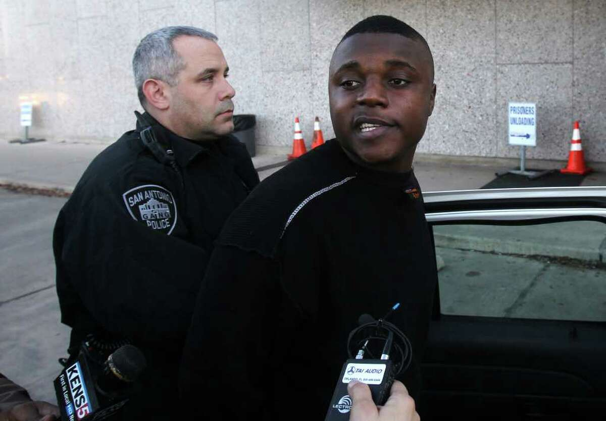 Jovon Flemings, 22, a suspect in several East Side shootings (center, black shirt) is led out of San Antonio Police headquarters Thursday morning. One of the shootings took place on Christmas day on Belmont street and another took place on Crockett street. The man is being charged with five counts of aggrevated assault.