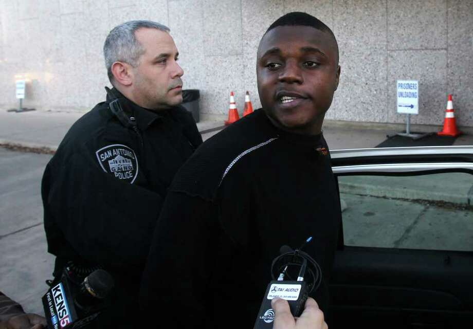 Jovon Flemings, 22, a suspect in several East Side shootings (center, black shirt) is led out of San Antonio Police headquarters Thursday morning. One of the shootings took place on Christmas day on Belmont street and another took place on Crockett street. The man is being charged with five counts of aggrevated assault. Photo: SAN ANTONIO EXPRESS-NEWS