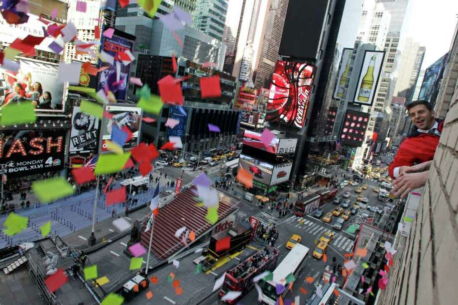 Times Square Alliance President Tim Tompkins throws a handful of confetti from eight stories above onto the streets of Times Square, Thursday, Dec. 29, 2011 in New York. The airworthiness test is in preparation for the release of one ton of confetti by hand from various buildings in Times Square at midnight on New Year's Eve.(AP Photo/Mary Altaffer) Photo: Mary Altaffer, Associated Press / AP