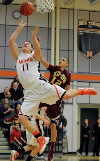 Grant Massaroni of Mohonasen drives to the basket past Dwayne Freeman, #12, of Bishop-Gibbons during