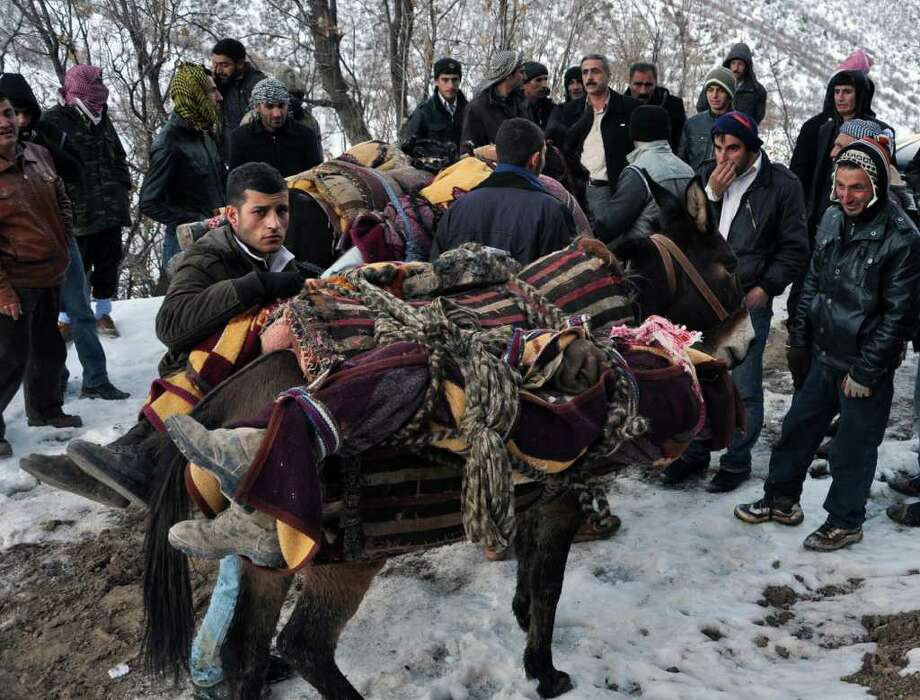 People mount bodies onto mules after Turkey's air force attacked suspected Kurdish rebel targets across the border in Iraq, killing at least 35 people, many of them believed to be smugglers mistaken for guerrillas, near the Turkish village of Ortasu in Sirnak, Turkey, Thursday, Dec. 29. 2011. The Turkish military confirmed the Wednesday night raids, but said its jets struck an area of northern Iraq that is frequently used by Kurdish rebels to enter Turkey, after drones detected a group approaching Turkey's border. (AP Photo) Photo: Associated Press / AP