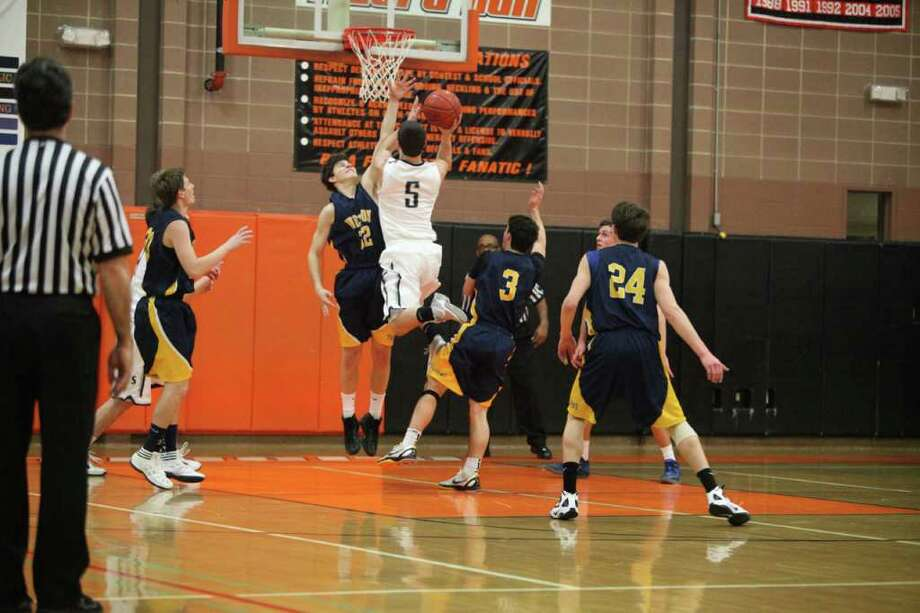 Weston's Troy Flynn attempts to block Staples' Vasili Tziolis' shot Tuesday in the first round of the Ridgefield Holiday tournament. Flynn had nine points and three steals in the Trojans' 57-56 victory. Photo: Vivian Simons / Contributed Phot