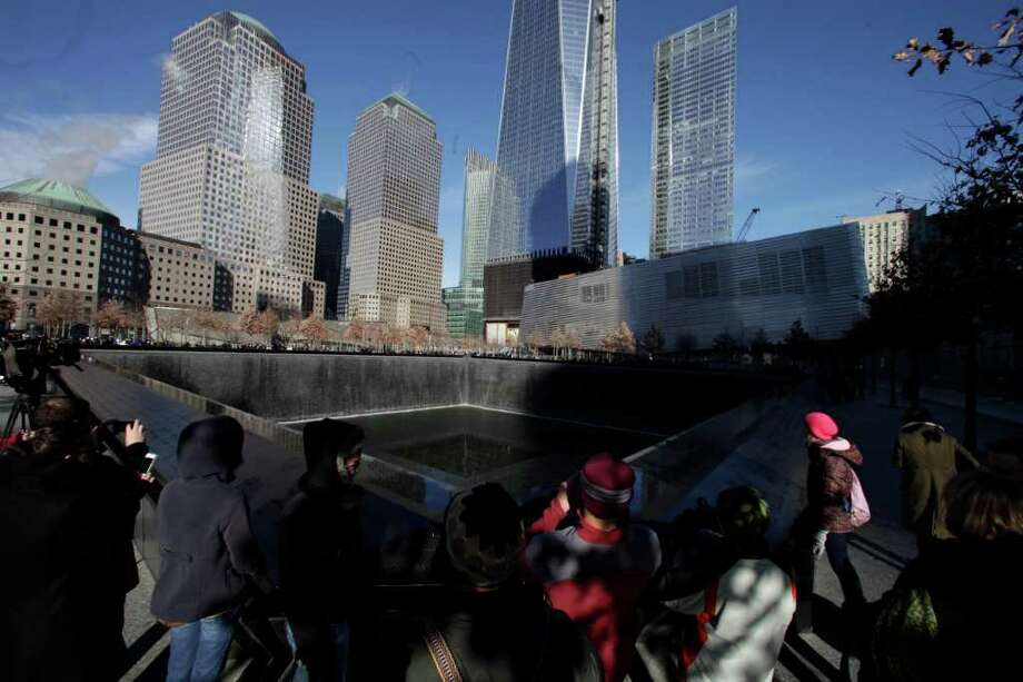 Visitors walk around the National September 11 Memorial, Thursday, Dec. 29, 2011 in New York. The memorial announced that it has had a million visitors since the site opened to the public in September. The museum entrance is at right. (AP Photo/Mark Lennihan) Photo: Mark Lennihan, Associated Press / AP