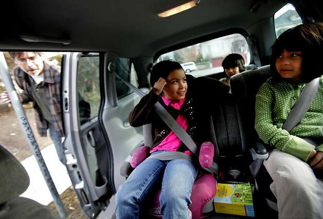 Twins Greer, left, and Scarlet Nakadegawa-Lee,  7, get settled in their booster seats before heading out in Oakland, Calif., Thursday, December 29, 2011.  Their father, Tadashi Nakadegawa, left, is happy the child safety seat laws have been extended.  The girls will now have to stay in the seats until they are eight, and he thinks this will keep them safer. Photo: Sarah Rice, Special To The Chronicle