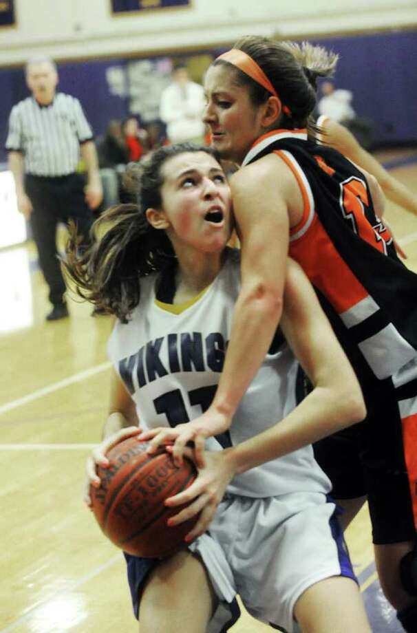 Westhill's Megan D'Allessandro draws a foul from Stamford's Kelsey Cognetta as Westhill High School hosts Stamford High in a girls basketball game in Stamford, Conn., December 29, 2011. Stamford was ahead at halftime with a score of 19-5 but Westhill rallied in the second half to win the game 36-35. Photo: Keelin Daly / Stamford Advocate
